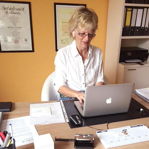 Bettina mit MacBook am Schreibtisch