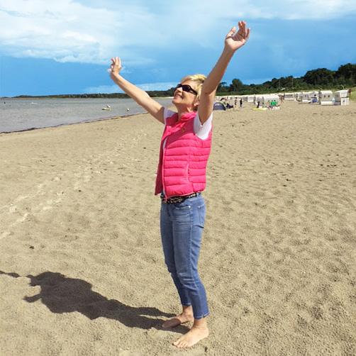 Bettina geniesst einen Tag am Strand und streckt die Arme zum Himmel