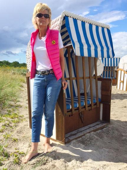 Bettina Schmidt lehnt stehend am Strandkorb am Meer. Das Gesicht zur Sonne gewendet.