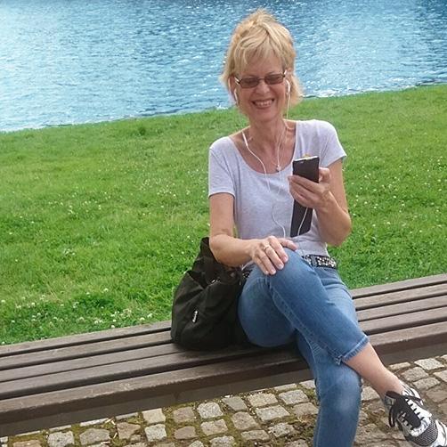 Bettina am iPhone auf Bank im Park im Sonnenschein